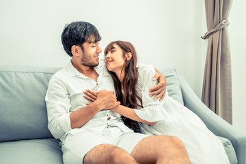 Happy young couple relaxing on sofa in living room