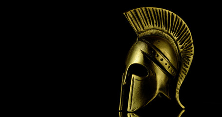 A wonderful golden Spartan helmet as part of the equipment of ancient greek soldiers. King Leonidas and his 300th The piece of metal stands against a black background