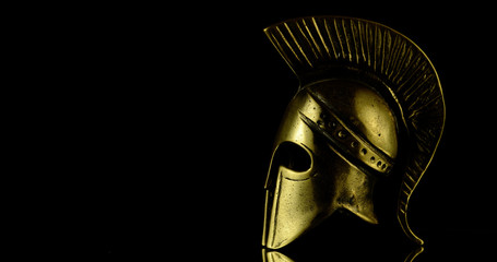 A wonderful golden spartan helmet as part of the equipment of ancient greek soldiers. King Leonidas and his 300th. The piece of metal stands against a black background
