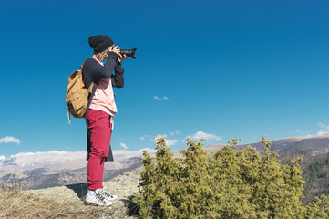 Nature Photographer taking pictures on his dslr camera outdoors during hiking trip on Caucasus. North Caucasus Russia