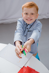 cheerful preschooler red hair boy with pencils sitting at table with paper for drawing in classroom