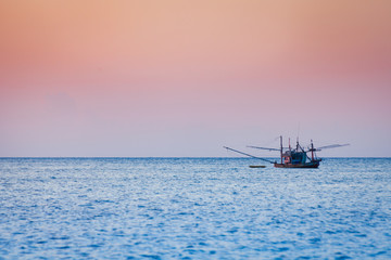 Fishing boat floating on the sea before sunset in Koh Phangan, Thailand.