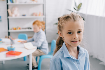 selective focus of smiling preschooler looking at camera with classmate behind at table in classroom