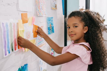 side view of african american child looking at camera while hanging colorful picture on white wall in room