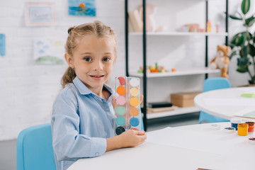 portrait of cute child showing paints in hands while sitting at table in room