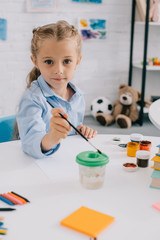 portrait of cute child sitting at table with paints and paint brush