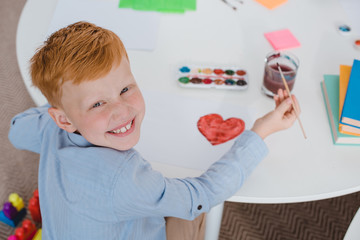 overhead view of happy red hair boy sitting at table with paints and paint brush for drawing in classroom