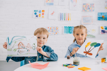 portrait of cute kids showing drawings in hands at table in classroom
