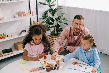 teacher in eyeglasses and multiracial children drawing pictures with paints at table in classroom