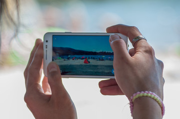 closeup of hands of woman taking a picture with smartphone on the beach