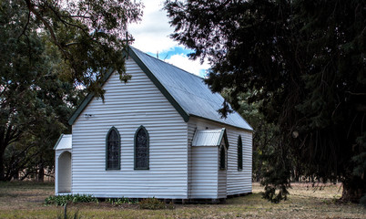 White historic vintage wooden rural country church surrounded by trees