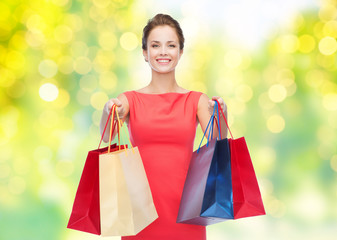 people and sale concept - beautiful smiling woman with shopping bags over green background and lights