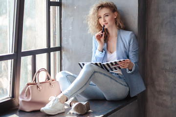 Pretty blonde young business woman sitting near window with planner notebook. Lifestyle casual portrait