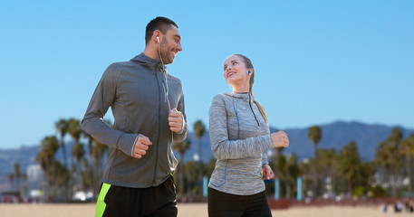 fitness, sport and technology concept - happy couple running and listening to music in earphones over venice beach background in california