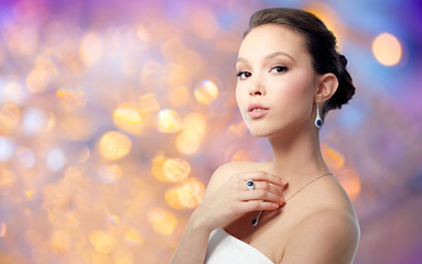 beauty, jewelry and luxury concept - beautiful asian woman or bride with earring, finger ring and pendant over holidays lights background