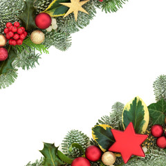 Christmas background border with red and gold star and ball bauble decorations, holly, fir, mistletoe and ivy isolated on white background.  Festive theme.