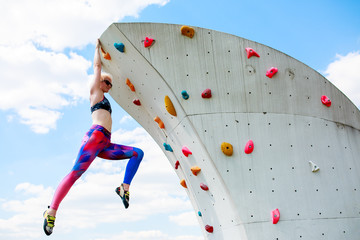 Photo of sporty woman in leggings hanging on wall for rock climbing against blue sky