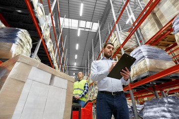 logistic business, shipment and people concept - businessman with clipboard and worker loading goods by forklift at warehouse