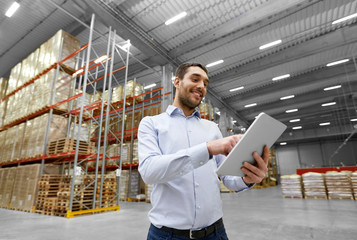 logistic business, shipment and people concept - happy businessman with tablet pc computer checking goods at warehouse