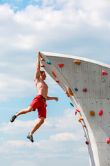 Photo of young sportive man hanging from top of climbing wall on summer