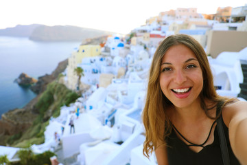 Europe travel selfie smiling girl in Oia village, Santorini. Cute happy smiling tourist girl taking self-portrait picture during summer vacation in famous European destination Santorini, Greece.