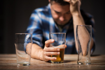 alcoholism, alcohol addiction and people concept - male alcoholic drinking beer from glass at night