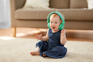 childhood, kids and technology concept - lovely redhead baby girl in headphones listening to music at home
