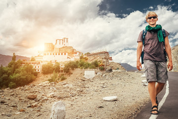 Young tourist man walks on road near Thiksey Monastery in India, Ladakh
