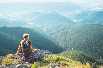Young man tourist backpacker sits on top on hill with beautiful valley panorama