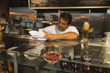 Male baker writing on a notepad at counter