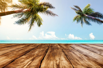 Table background of dark brown color and landscape of beach with sea and two palms.