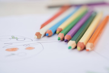 Close-up set of different colored pencils and child painting on paper