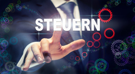 """A businessman pressing a Taxes """"Steuern"""" button in German on a futuristic computer  display"""