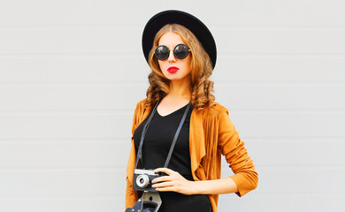 Cool girl model with retro film camera wearing elegant hat, brown jacket posing outdoors over city grey background