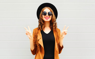 Cool girl wearing a black hat, sunglasses and jacket over urban grey background