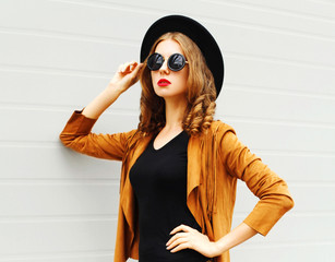 Beautiful woman model wearing a black hat, sunglasses and jacket looking in profile over urban grey background
