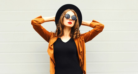 Elegant woman model wearing a black hat, sunglasses and jacket over urban grey background