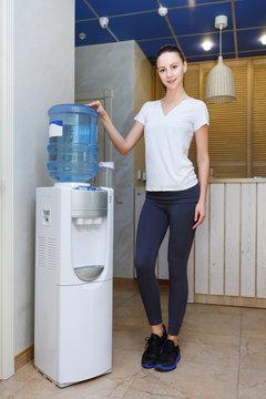 Woman, 20s, caucasian, standing at water cooler wearing sportwear