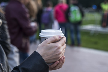 A disposable glass in the hands of a woman. Disposable paper cup for coffee, tea.