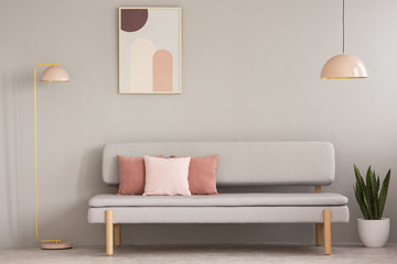 Real photo of grey sitting room interior with couch with cushions, pastel pink lamps, fresh plant and simple poster on the wall