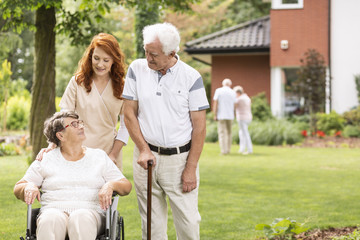 Nurse and grandmother in the wheelchair next to elderly man with walking stick