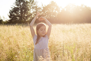 Young girl standing in field at summer evening