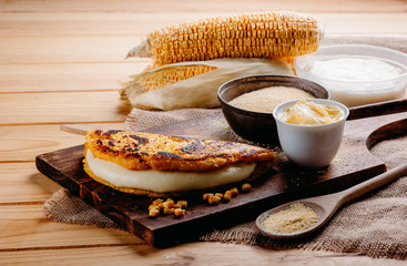 Wooden table with several ingredients for the preparation of Cachapas with cheese, corn, butter, ground corn and white cheese, Venezuelan Cuisine