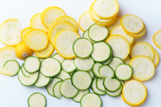 Top view of sliced summer yellow squash and zucchini on white background