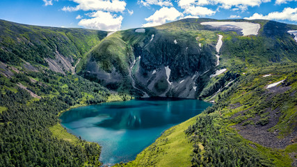 Blue lake in the mountains green grass and snow Ivanovo lakes