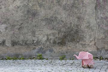 Origami elephant on cobblestones, concrete wall