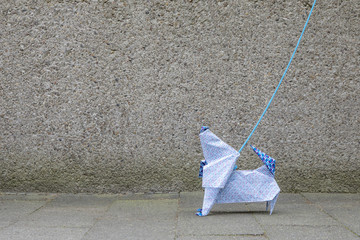 Origami dog in front of concrete wall