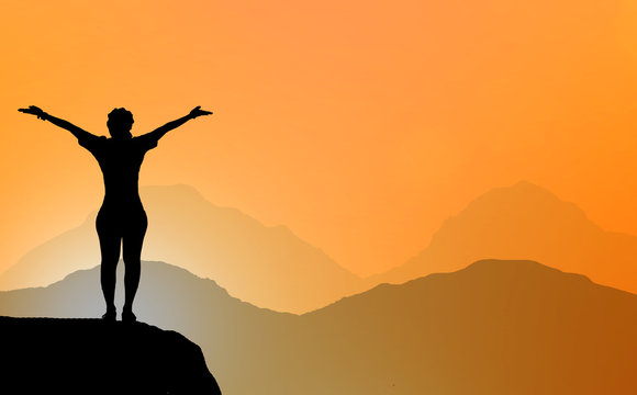silhouette Woman standing on a mountain with two hand  on blurry sunrise