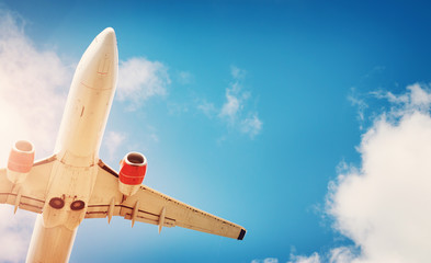 plane at landing on blue sky background with white clouds. Airplane turbine and wing view