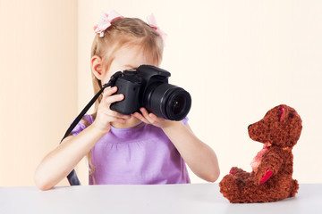 A little girl is taking pictures of a toy bear